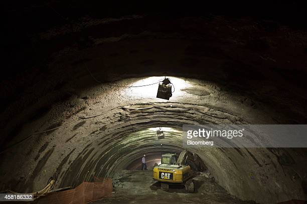 A worker operates a Caterpillar Inc excavator during the final stage of construction on the Tunnel Rio 450 project in Rio de Janeiro Brazil on...