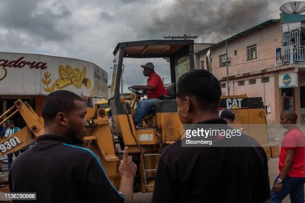 Worker operates a Caterpillar Inc. Loader as people gather near the Venezuelan border in Pacaraima, Brazil, on Wednesday, April 10, 2019. Venezuelan...