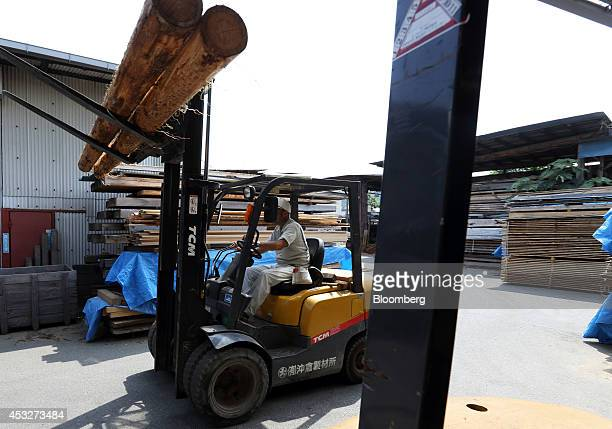 A worker operates a folk lift transporting logs at the Okikura Lumber Mill facility in Akiruno City Tokyo Japan on Friday Aug 1 2014 Along with...