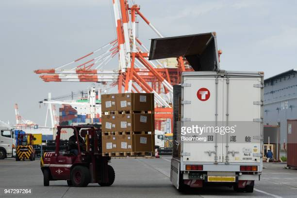 A worker operates a forklift to load boxes of goods onto a Takada Unyu KK truck at a shipping terminal in Yokohama Japan on Monday April 16 2018...