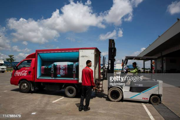 A worker operates a forklift to load CocaCola Co brand drinks onto a truck at the CocaCola Cambodia Bottling Plant operated by Cambodia Beverage Co...