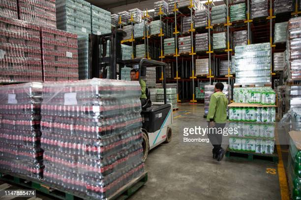 A worker operates a forklift to move bottles of CocaCola Co brand Coke carbonated soft drink inside a warehouse at the CocaCola Cambodia Bottling...