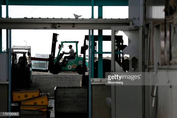 A worker operates a forklift to move ice at a fishing port in Ishinomaki Miyagi Prefecture Japan on Sunday June 16 2013 Haruhiko Kuroda governor of...