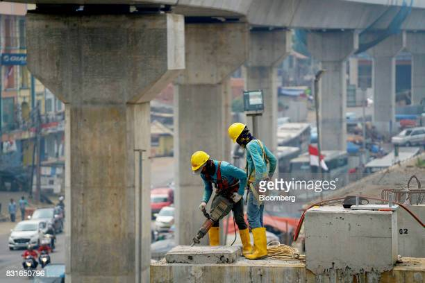 A worker operates a jackhammer on a support column of an elevated track for the Jakarta Mass Rapid Transit under construction in Jakarta Indonesia on...