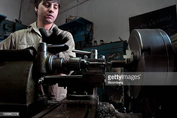 A worker operates a lathe to shape components for agricultural seeders being manufactured at the Metalurgica Eraso factory in Pergamino Argentina on...
