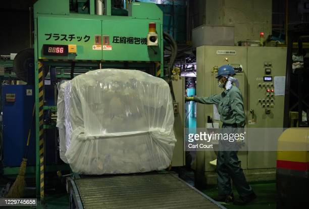 A worker operates a machine that packs bales of household plastic waste into plastic bags for transportation at Minato plastic household waste at...