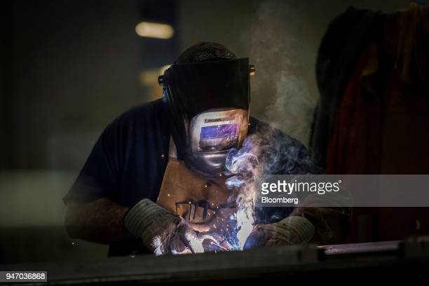 A worker operates a metal inert gas welder to join seams at the Metal Manufacturing Co facility in Sacramento California US on Thursday April 12 2018...