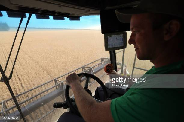 A worker operates a Torum combine harvester manufactured by Rostselmash OJSC as it drives through a wheat field during the summer harvest on a farm...