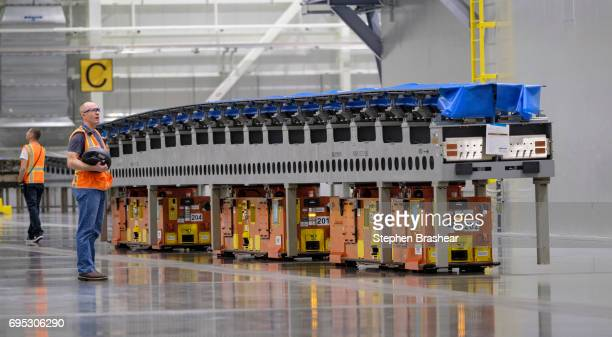 A worker operates an automated guided vehicle carrying a wing part through the Boeing 777X Composite Wing Center on June 12 2017 in Everett...