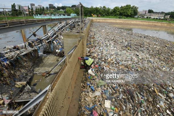 A worker operates at a barrage where plastic waste is prevented to reach the Ebrie lagoon in Abidjan on June 2 2018 On June 5 2018 the United Nations...