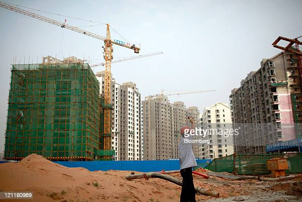 A worker operates on a construction site for new residential housing in Yulin Shaanxi Province China on Sunday Aug 14 2011 Chinese regulators have...