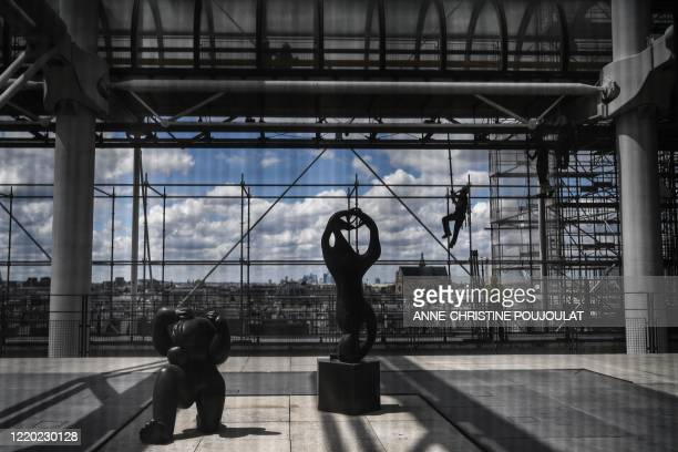 Worker operates on the facade of the Centre Georges Pompidou modern art museum, currently closed to the public, on June 15, 2020 in Paris, aimed to...
