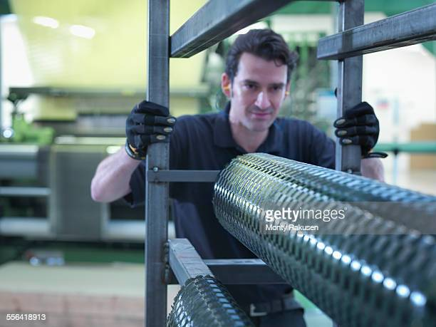 Worker operating carbon fibre loom in carbon fibre factory