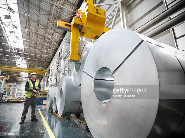 worker operating crane with steel rolls in car factory - aço - fotografias e filmes do acervo