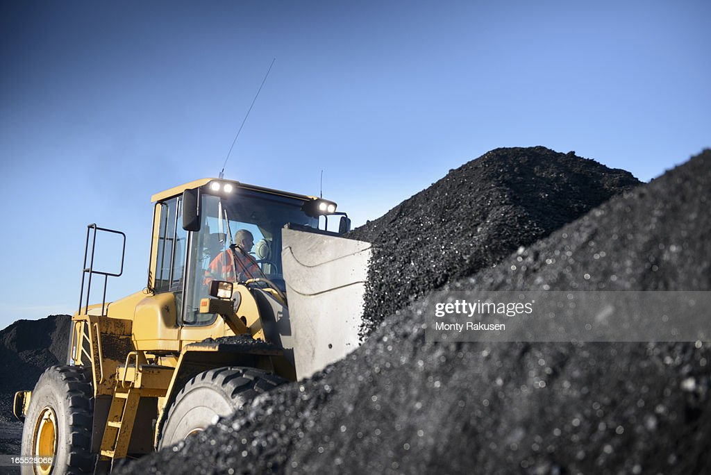 Worker operating digger with pile of coal at surface coal mine : Stock Photo