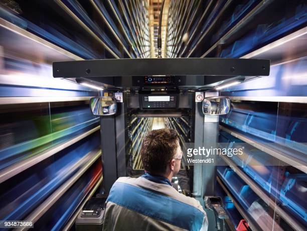 worker operating high rack in storehouse - automation stock pictures, royalty-free photos & images
