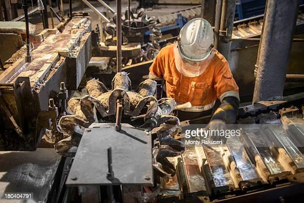 Worker operating ingot casting machine in aluminium foundry