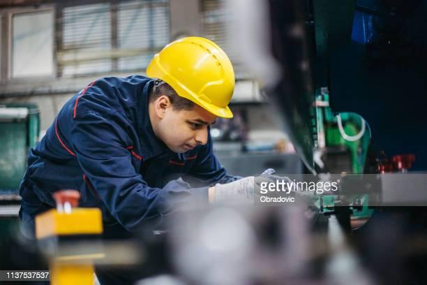 trabalhador operando máquina de imprensa da folha de metal - maquinaria - fotografias e filmes do acervo