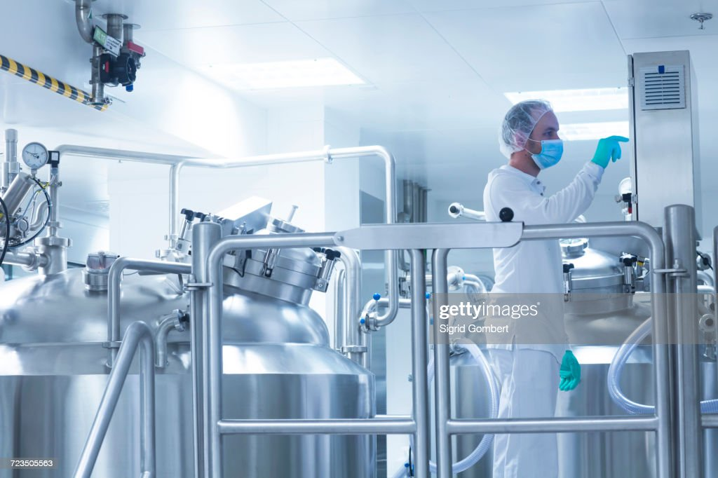 Worker operating pharmaceutical production equipment in pharmaceutical plant : Stock-Foto