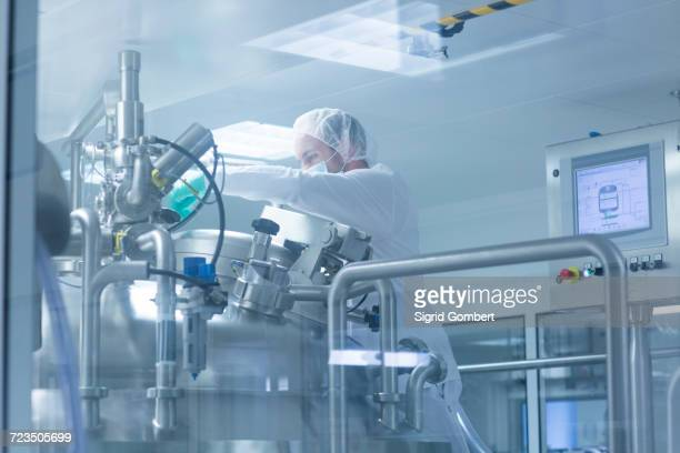 worker operating pharmaceutical production equipment in pharmaceutical plant - sigrid gombert stock-fotos und bilder