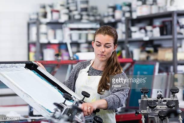Worker operating silkscreen machine