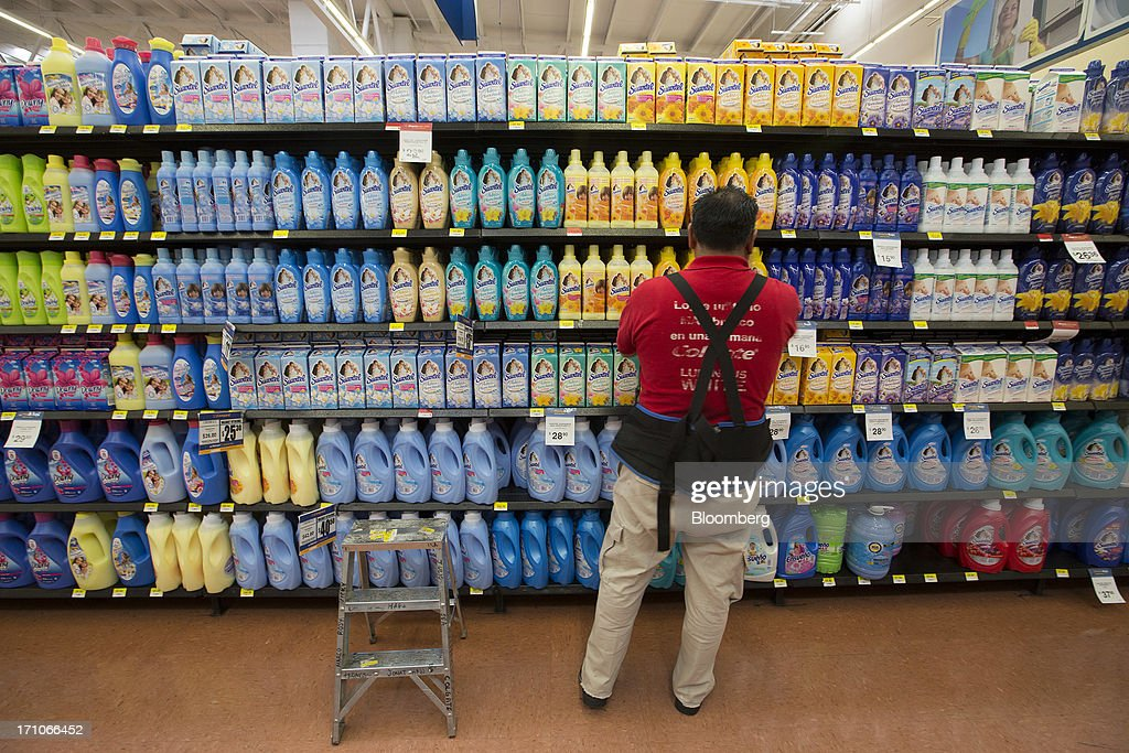 A Worker Organizes Laundry Detergent On A Shelf At A Wal
