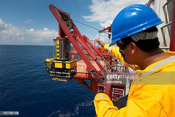 A worker overlooks the descent of an iTech remotely operate vehicle on the Petroleos Mexicanos Bicentennial deep sea crude oil platform in the waters...