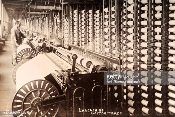 A worker overseeing the beaming process in a textile manufacturing factory in Lancashire circa 1920
