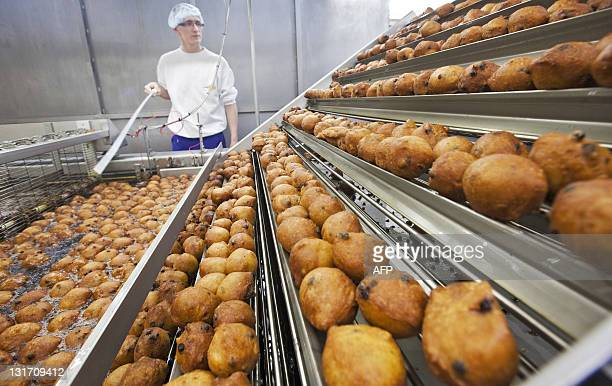A worker oversees the production of traditional Dutch food known locally as 'oliebollen' at a bakery in Beverwijk on November 7 2011 The bakery...