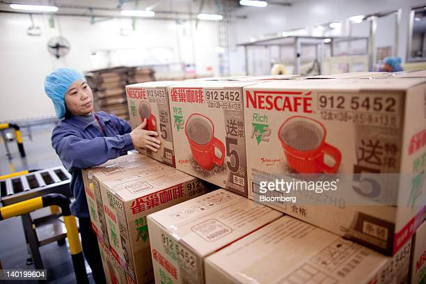 A worker packages Nescafe at Nestle SA's production facility in Dongguan Guangdong Province China on Tuesday Feb 28 2012 Nestle the world's biggest...