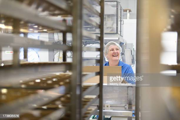 Worker packing biscuits in food factory