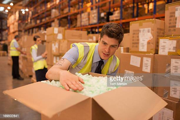 worker packing box in warehouse - polystyrene stock pictures, royalty-free photos & images
