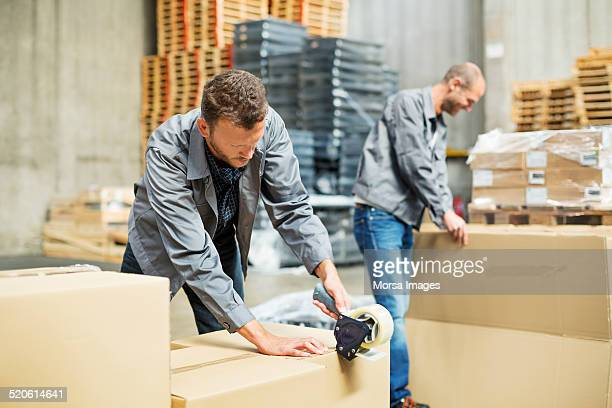 worker packing cardboard boxes in warehouse - pack fotografías e imágenes de stock