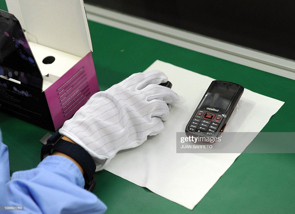 A worker packs a mobile at he assembly line of Venezuelan-Chinese mobile phones manufacturer Orinoquia, in Caracas, May 21, 2010. AFP PHOTO/Juan BARRETO