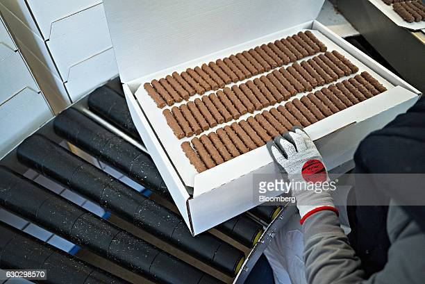 A worker packs bars of Cailler branded 'branche' chocolate on the production line at the Nestle SA production facility in Broc Switzerland on Monday...