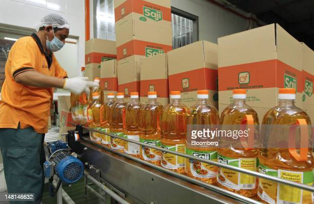 A worker packs bottles of Saji brand cooking oil at the Delima Oil Products Sdn Bhd refinery a subsidiary of Felda Global Ventures Holdings Bhd in...