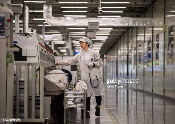 A worker packs up new smartphone devices at the end of the production line at Huawei's production campus on April 11 2019 in Dongguan near Shenzhen...