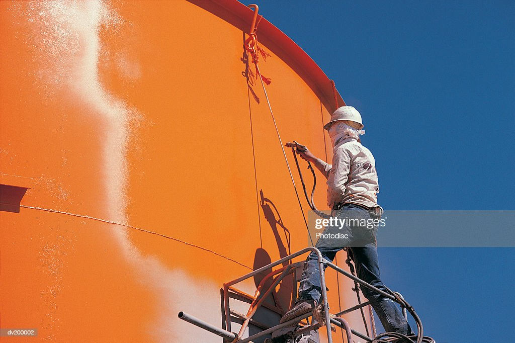 Worker painting storage tank : Stock Photo