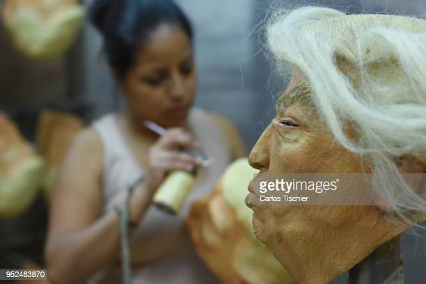 A worker paints a mask of US President Donald Trump during the finishing process of latex masks manufacturing at REV Latex Mask factory on April 27...