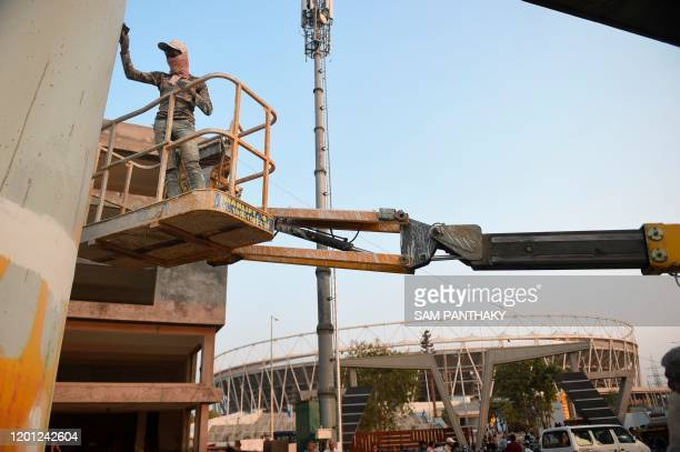 A worker paints a pillar of the under construction metro rail project outside the Motera Cricket Stadium on the outskirts of Ahmedabad on February 16...