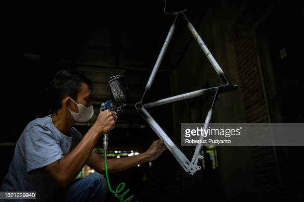 Worker paints a Spedagi frame at Piranti Works workshop on June 02, 2021 in Temanggung, Indonesia. The Spedagi Bamboo Bike takes advantage of the...