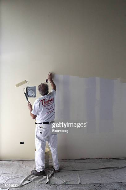 Worker paints a wall inside a new Whole Foods Market Inc. Store under construction in Park Ridge, Illinois, U.S., on Tuesday, Sept. 17, 2013. Whole...