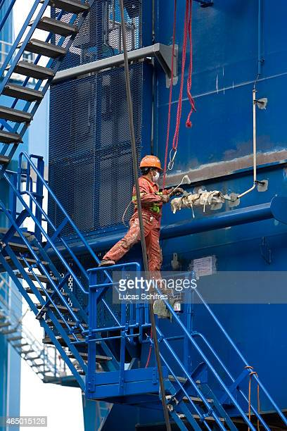 A worker paints an industrial crane just out of the workshops of Shanghai Zhenhua Port Machinery Co Ltd on December 8 2009 in Changxing Island...