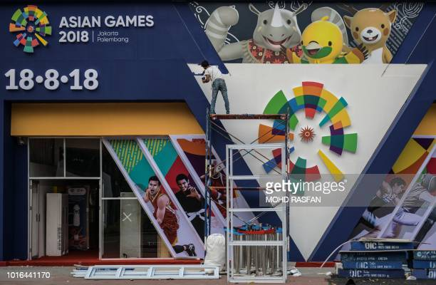 A worker paints an installation showing mascots Kaka Bhin Bhin and Atung ahead of the 2018 Asian Games in Jakarta on August 14 2018