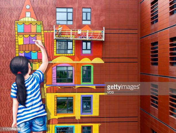 Worker paints on the wall of Jiangsu Women and Children Health Hospital on September 4, 2019 in Nanjing, Jiangsu Province of China. The wall painting...