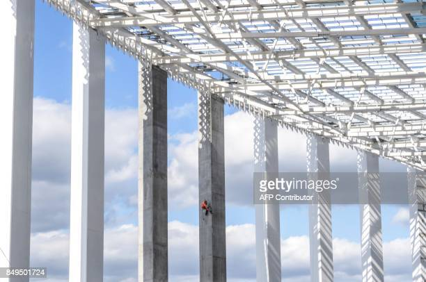 A worker paints one of the giant columns at the Nizhny Novgorod Stadium in Nizhny Novgorod on September 19 2017 The arena will host several football...