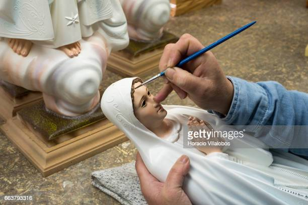 A worker paints statuettes of Virgin Mary at Farup a leading local manufacturer of religious articles on March 31 2017 in Fatima Portugal The...