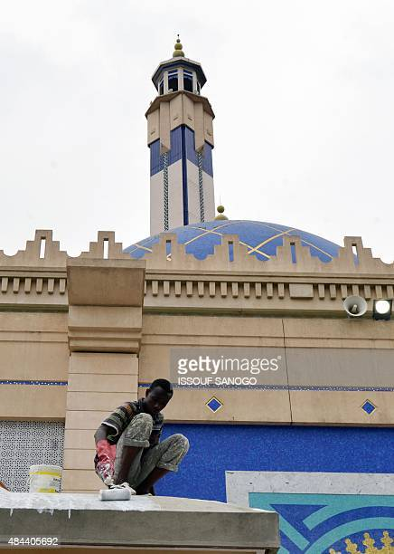 A worker paints the Great Mosque in the central business district of Le Plateau in Abidjan on August 18 2015 AFP PHOTO / ISSOUF SANOGO