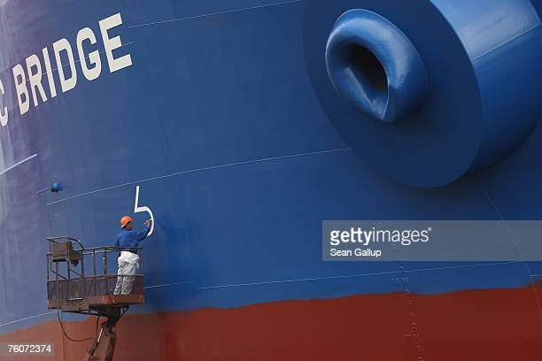 A worker paints the hull of a ship at the Blohm Voss shipyard August 13 2007 in Hamburg Germany Northern Germany with its busy ports of Hamburg...