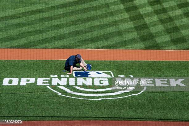 Worker paints the MLB logo of the field during a media tour of Nationals Park ahead of Major League Baseball Opening Day to explain the health and...